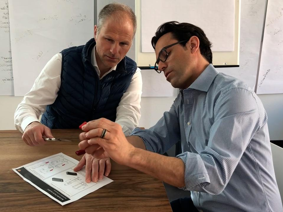 Andy Macaluso and Daneil Schlaepfer sit at a table looking at diagrams.