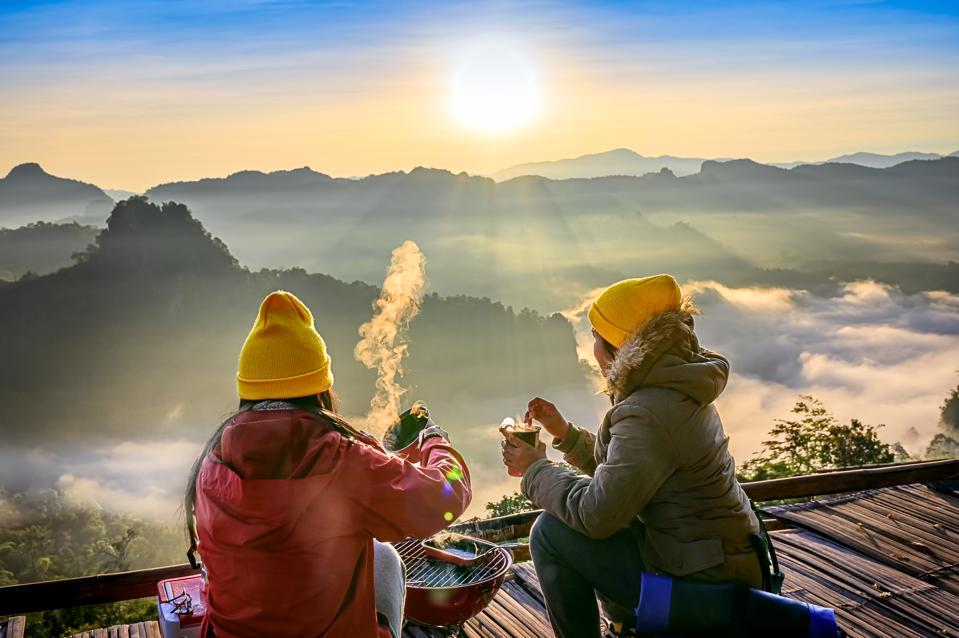 two women in winter coats looking over mountains