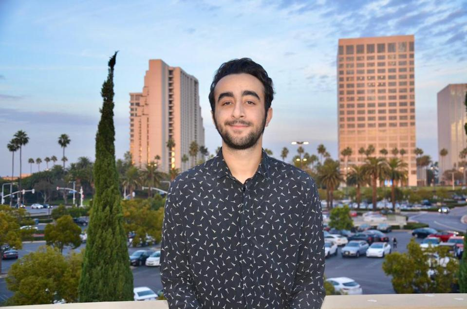 Portrait of young man in front of cityscape.