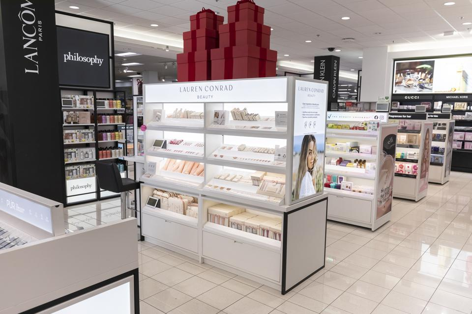 The clean, white beauty department of a Kohl's store with Lancôme Philosophy and Lauren Conrad Beauty displays.