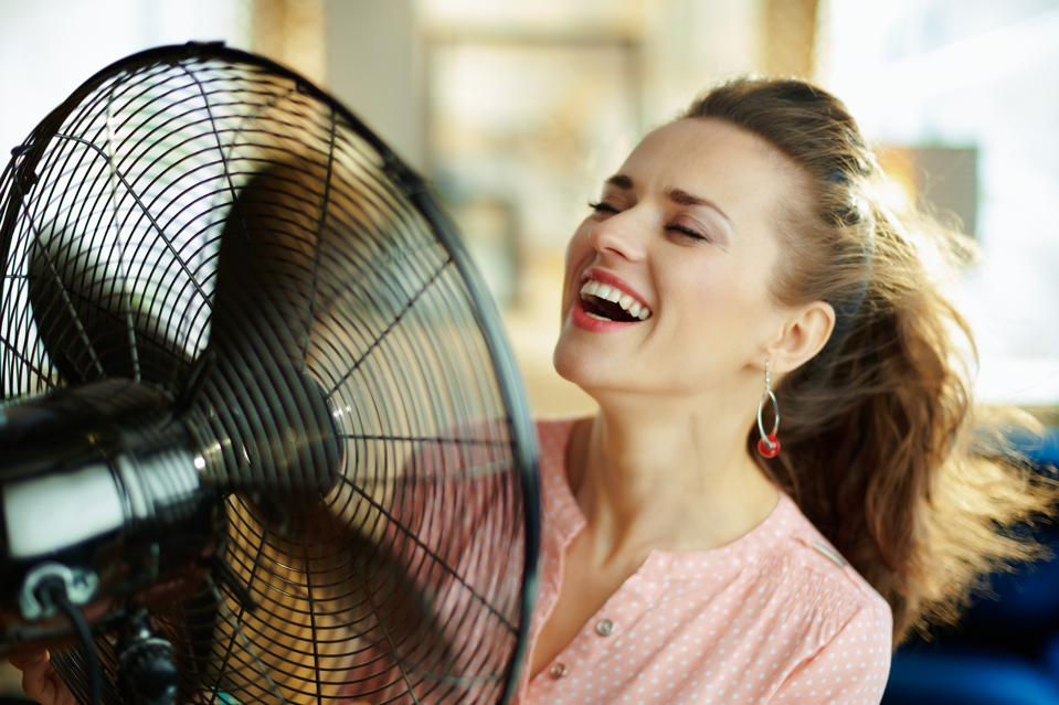smiling stylish housewife using electric floor standing fan