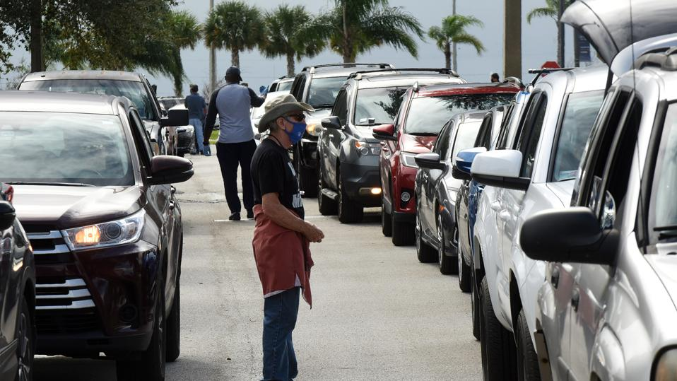 Volunteers direct traffic as residents line up in their cars...