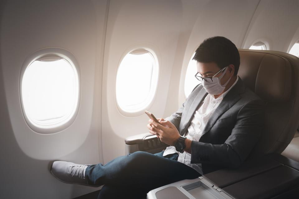 Young asian businessman wearing protective face mask with suit sitting in business first class seat using smartphone due to Coronavirus or COVID-19 outbreak situation in all of landmass in the world