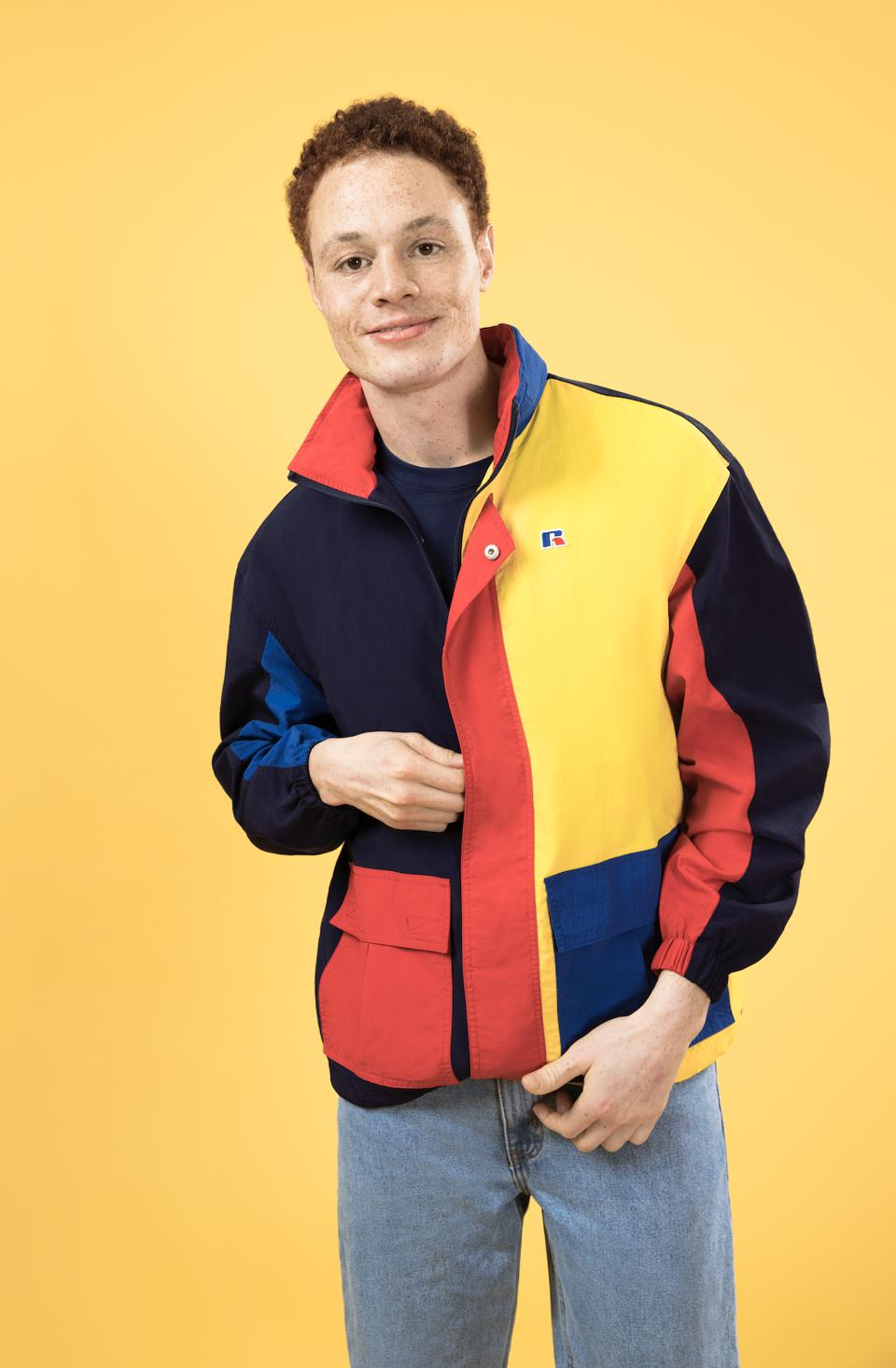 A 90's inspired look with vibrant color blocking and classic branding. Featuring a nylon shell with mesh lining and adjustable hood that stows inside the collar. Making your transition to Spring easy.