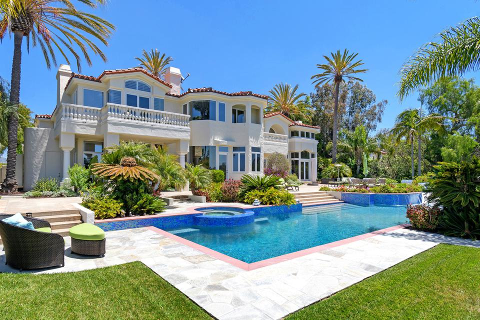 Tropical landscaping surrounds a blue-tiled swimming pool and home near San Diego.