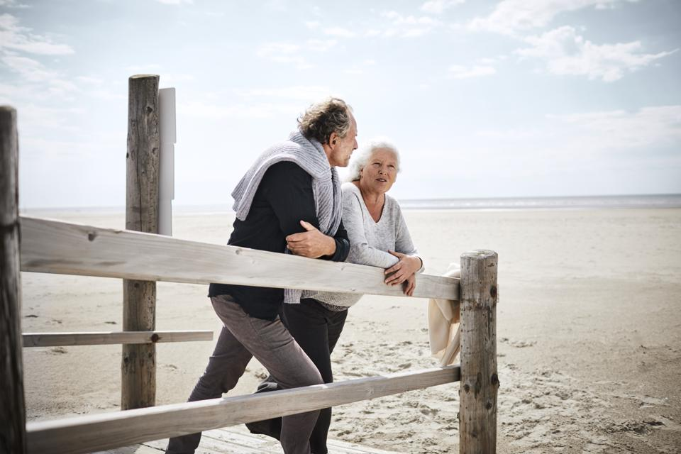 Senior couple standing on boardwalk on the beach
