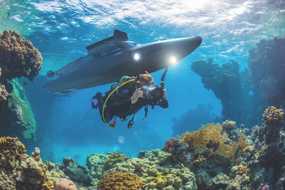 A scuba diver dives alongside the Victa submarine