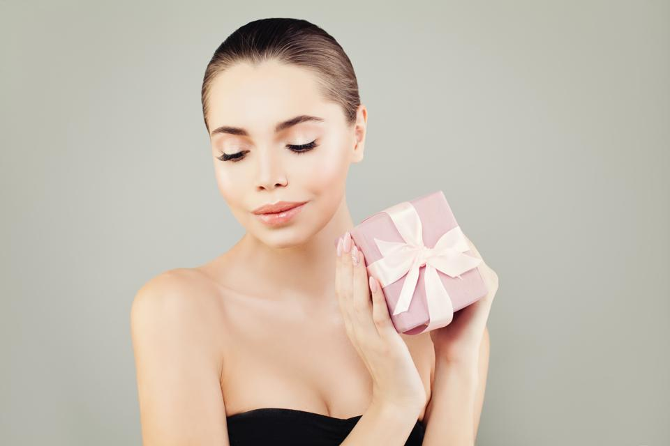 Nice Woman Holding Gift with Pink Ribbon on Gray Backgroung