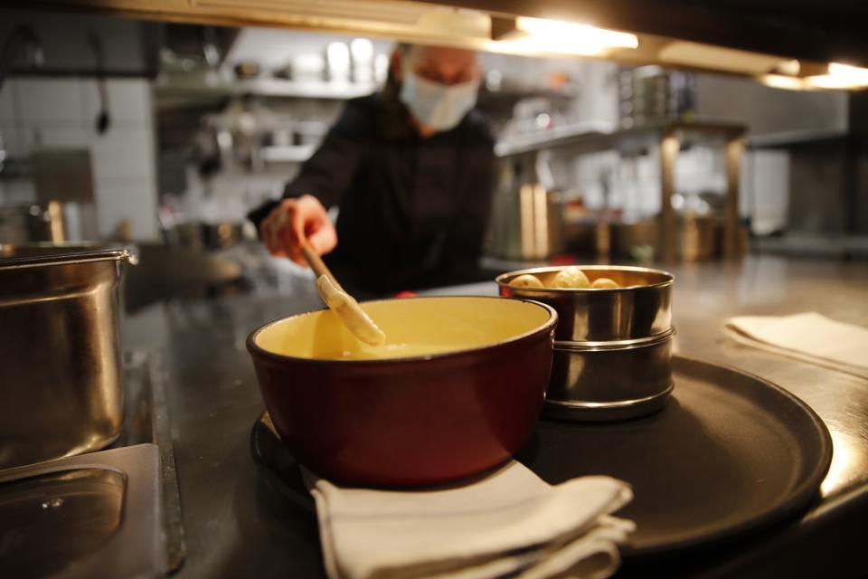 Preparing a beloved fondue in a ″caquelon″ pot at Restaurant Marzilibruecke in Bern, Switzerland on November 16, 2020.