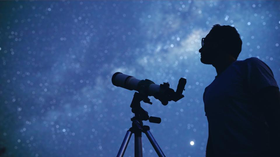 Astronomer with a telescope watching at the stars and Moon.