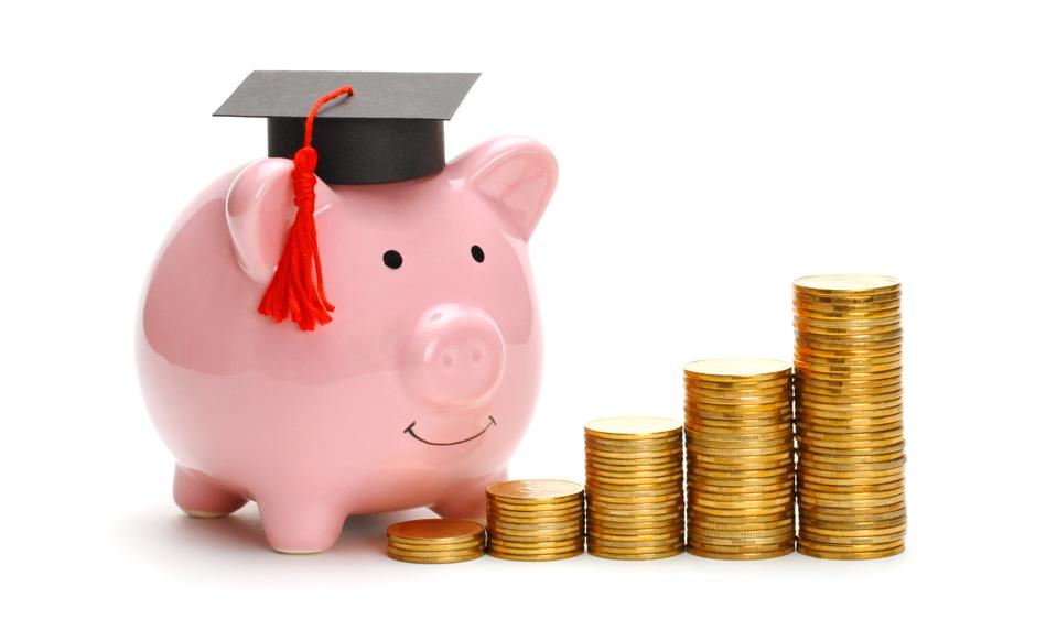 Piggy bank in graduate cap near stack of coins