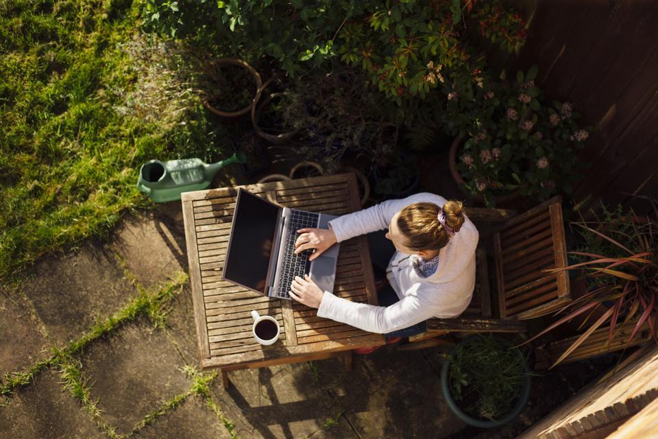 Mujer que trabaja desde casa en su jardín