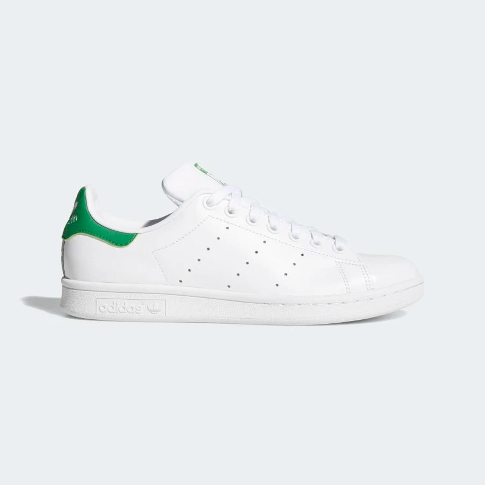 Adidas white Stan Smith shoes with green detail.