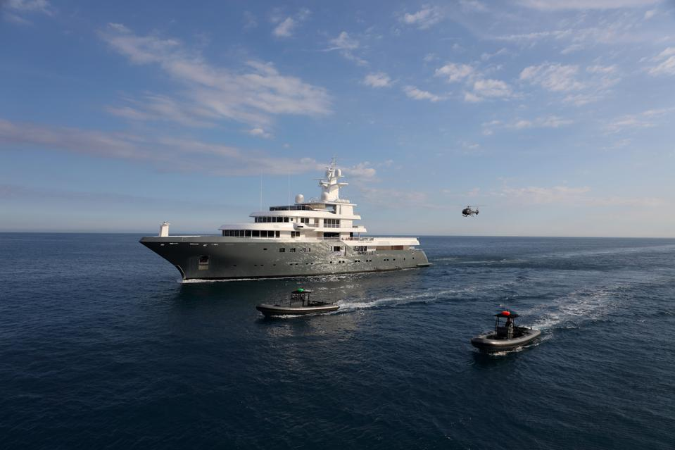 Planet Nine superyacht sails on the ocean, accompanied by custom tenders and a helicopter