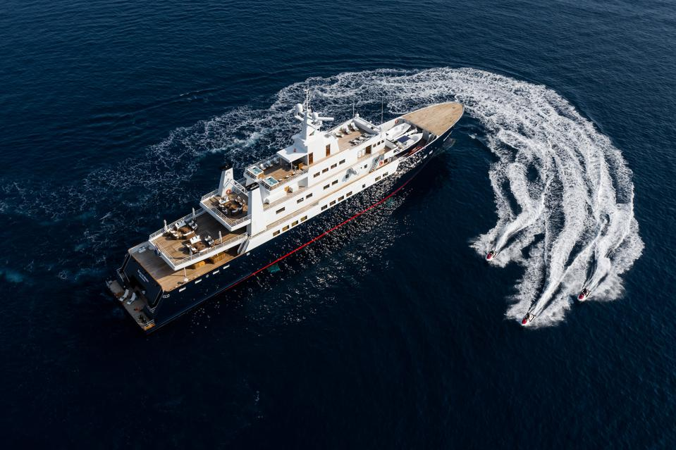 Bleu de Nîmes yacht sails on the ocean, surrounded by her tenders