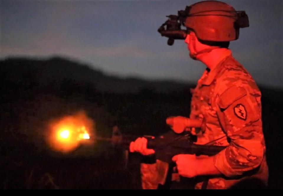 Soldier with headset firing rifle
