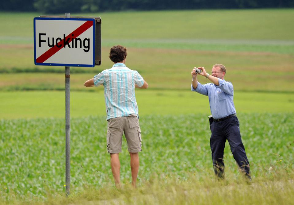 Tourists take pictures of the road sign of the village of Fucking, Austria