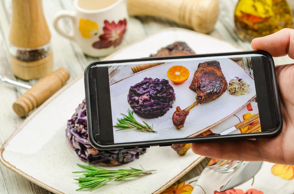 Young man taking photo of roasted duck leg dish on smartphone.