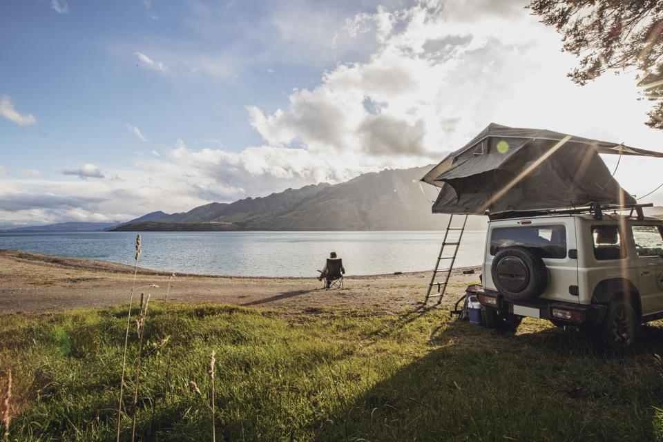 A woman sits along a lake next to a SUV with a tent in New Zealand