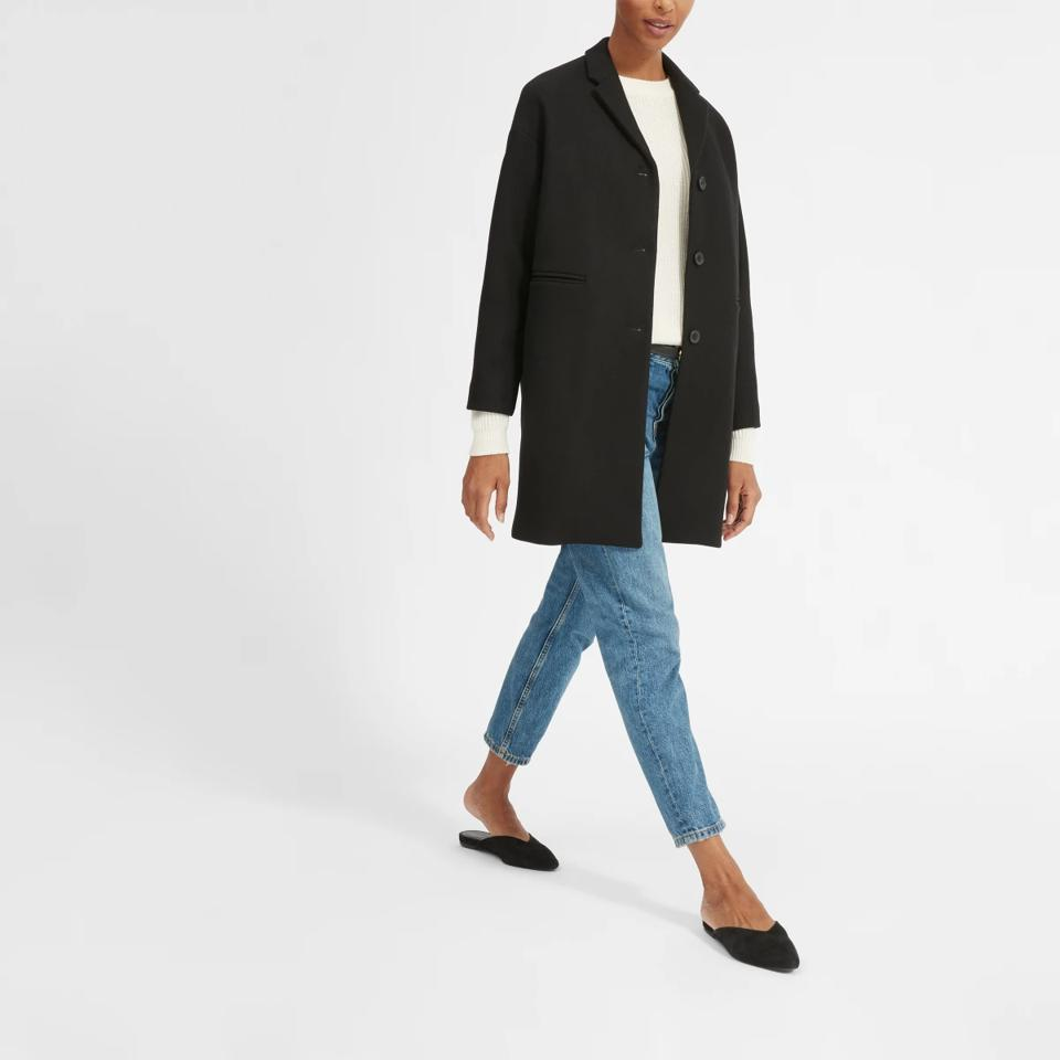 Everlane model in blue jeans and black wool coat.