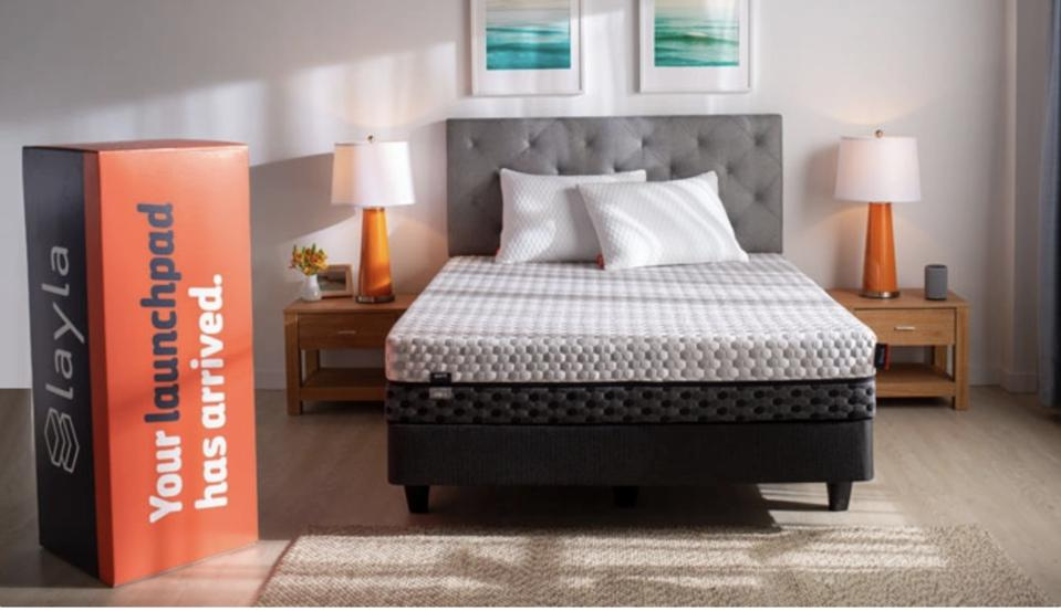 Layla mattress set up on a bed with it's shipping box next to it