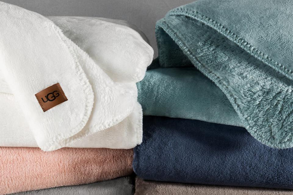a stack of Ugg Whistler throw blankets in several different colors.