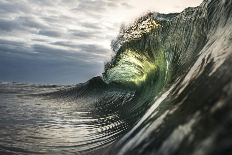 Large green wave breaking in ocean