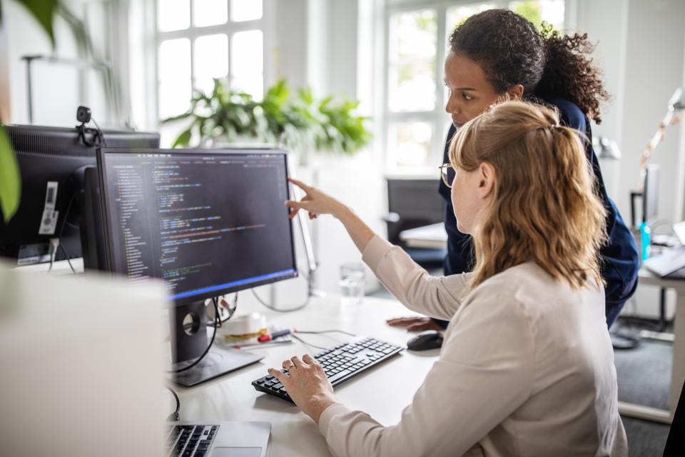 Coworkers discussing computer program in office
