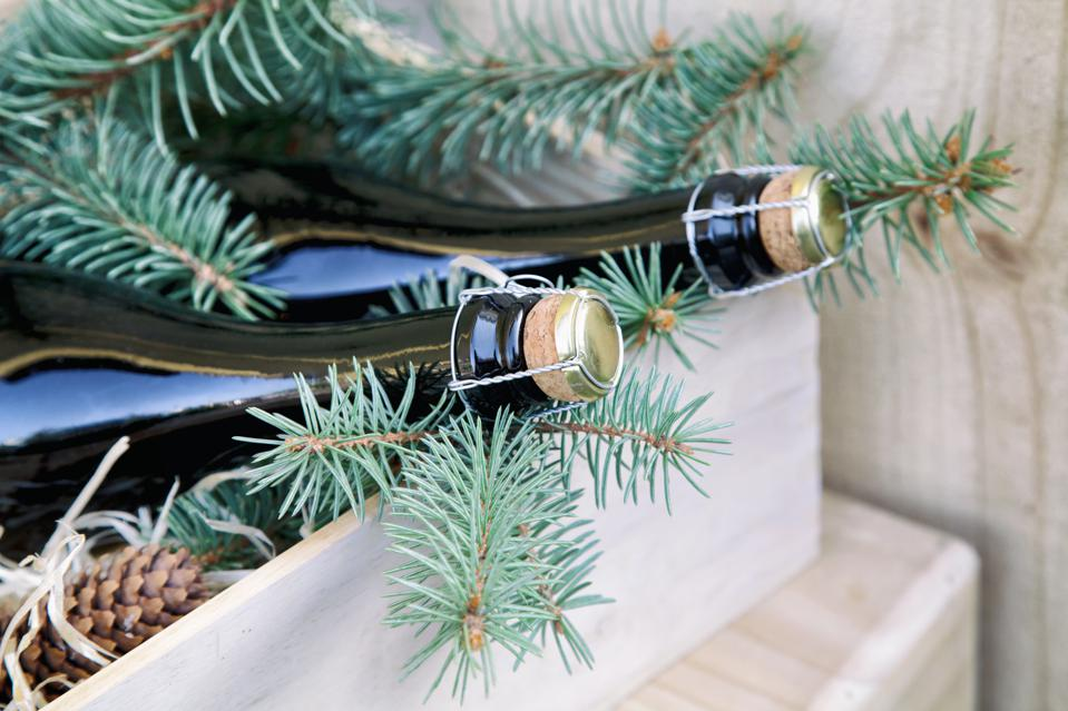 sparkling wine bottles and Christmas decor in a wooden box for delivery, New Year holidays