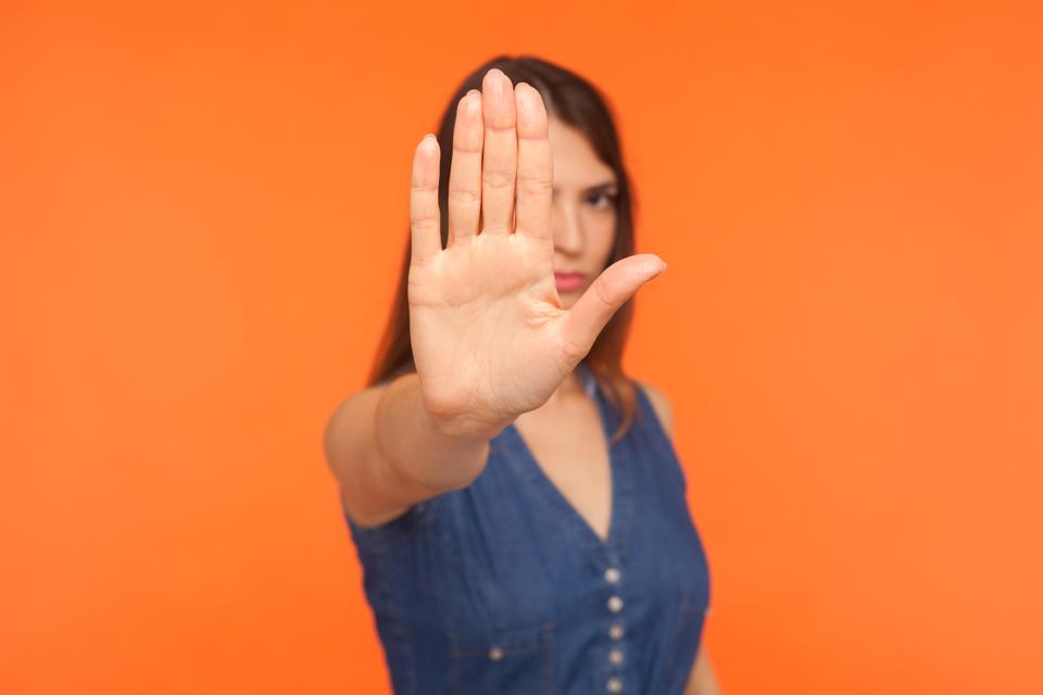 Prohibited! Strict brunette girl with serious bossy expression raising hand and showing stop