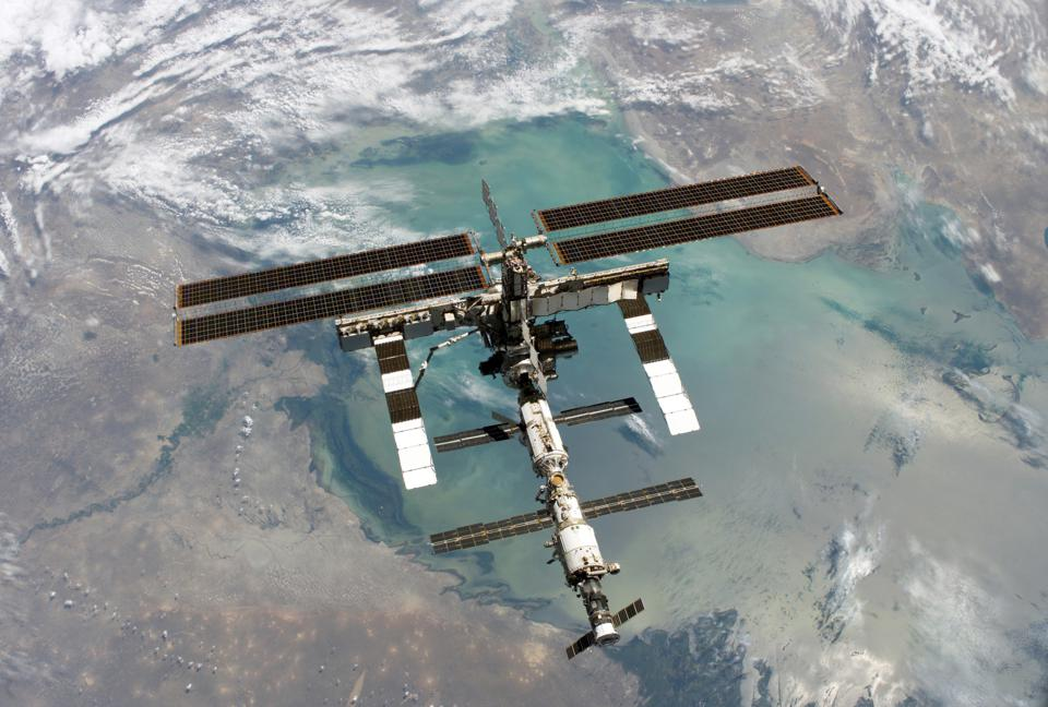 Backdropped by a colorful Earth, this complete view of the International Space Station was photographed by the Space Shuttle Discovery during the STS-114 Return to Flight mission, following the two spacecraft undocked.