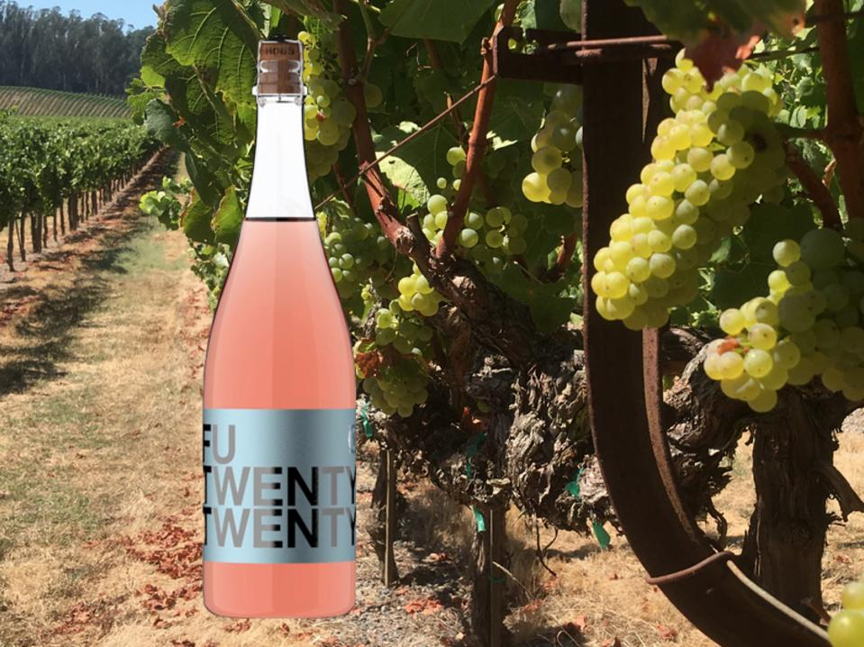 a bottle of pink rose wine sits in front of a row of white grapes
