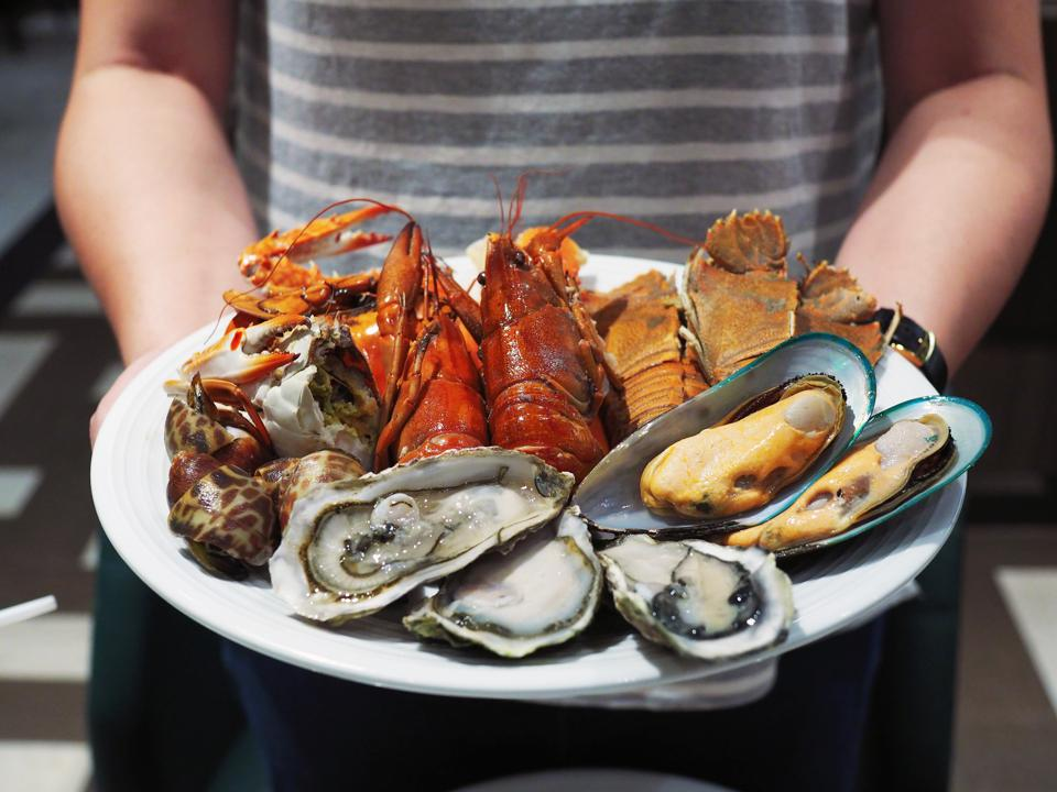 Plate of shellfish, including mussels, oysters, prawns, and shrimp.
