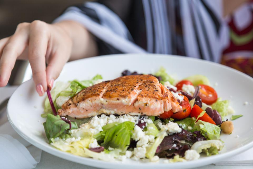A person eating a salmon fillet on top of a salad.
