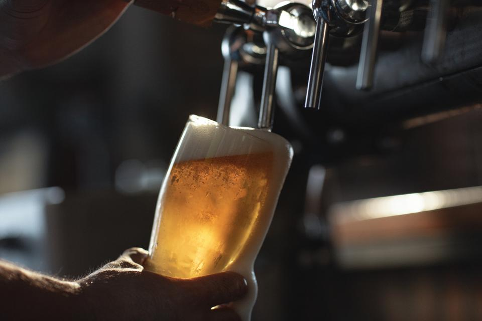 A person filling up a pint of beer from a tap.