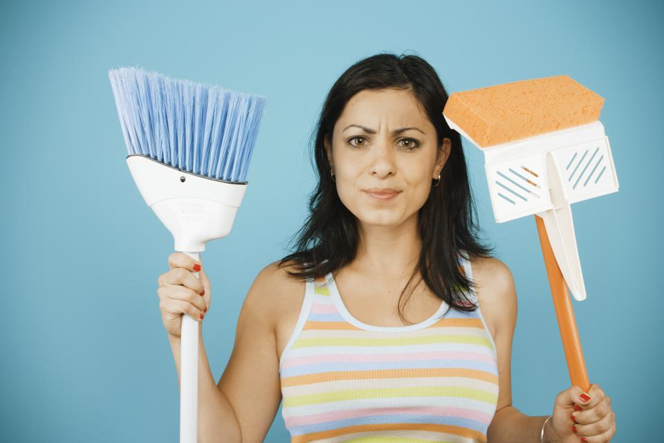 Young woman holding mop and broom.