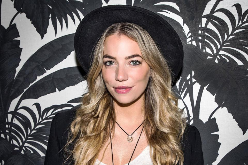 Headshot of Megan in front of black and white background wearing a hat.