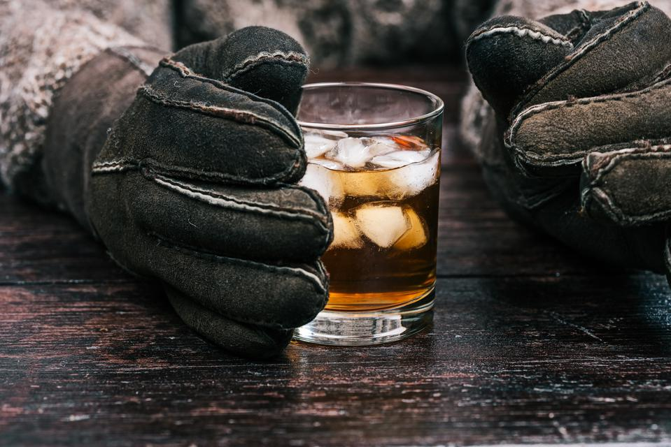 Hands holding whiskey winter