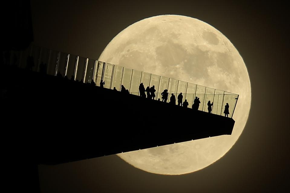 A full Moon rises behind people standing on the Edge, the outdoor observation deck in Manhattan, New York City on November 29, 2020.