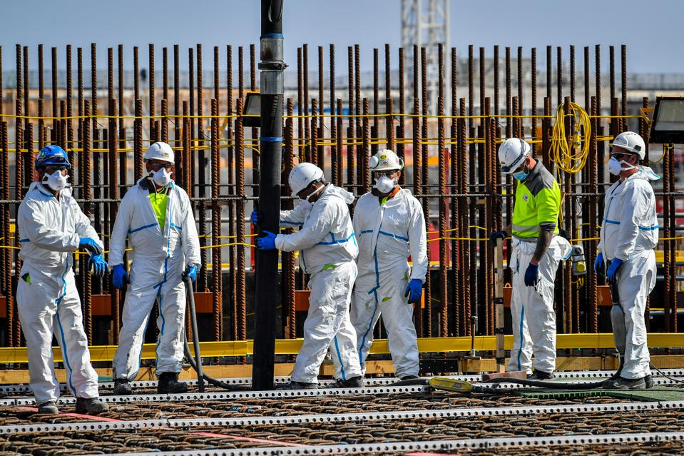 A team of workers pour concrete at the Hinkley Point C nuclear power station in England.