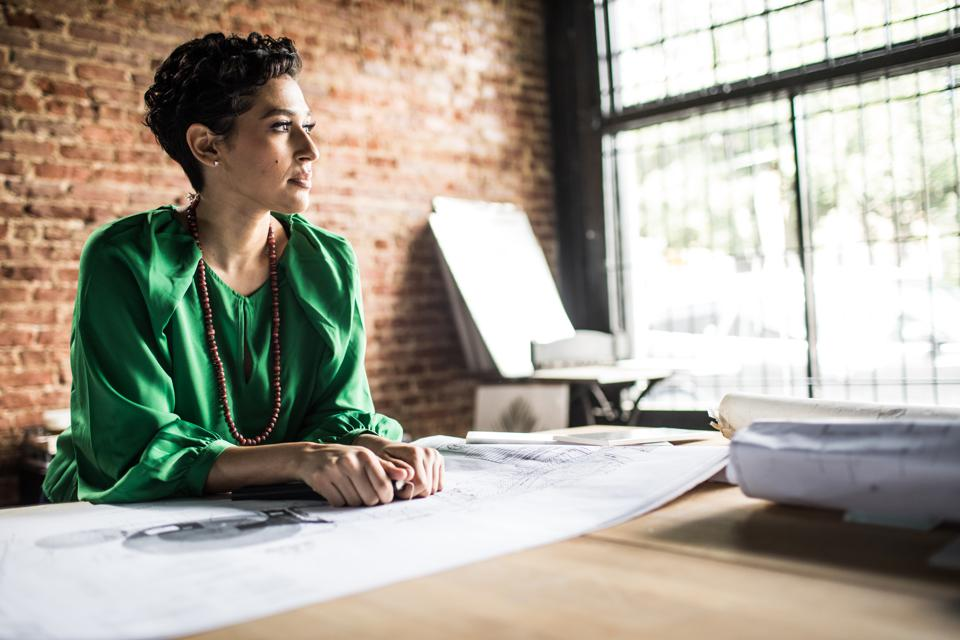 Portrait of Businesswoman looking over architecture blueprints in office