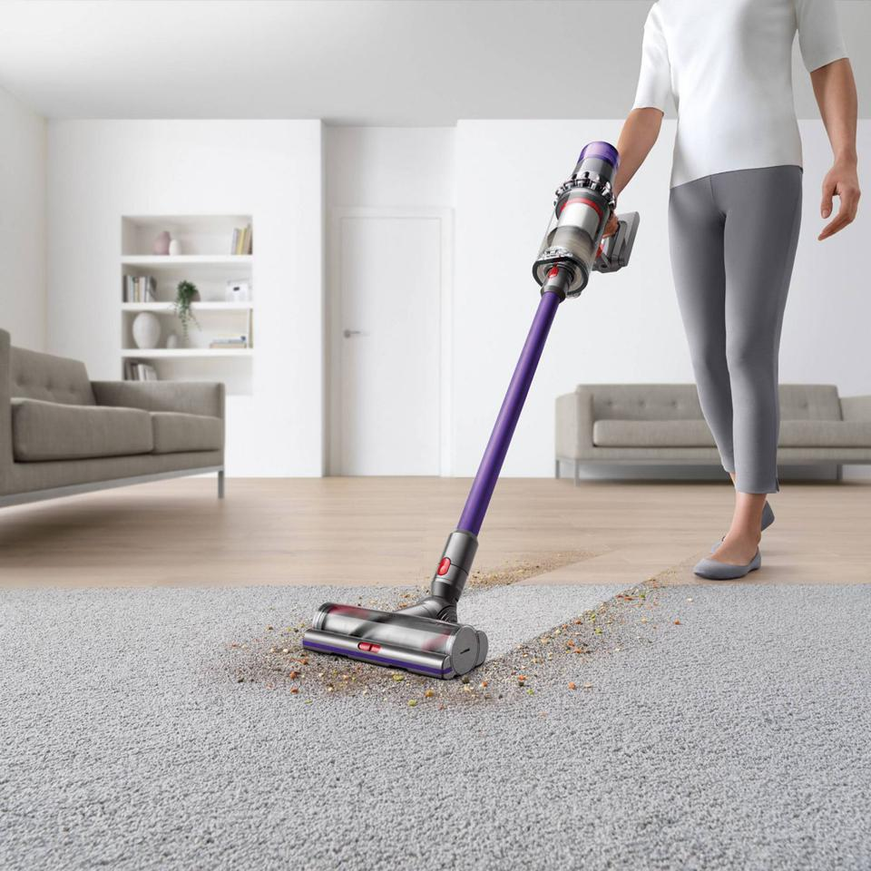 Woman vacuuming her carpet with the Dyson V11 Animal Cordless Stick Vacuum.