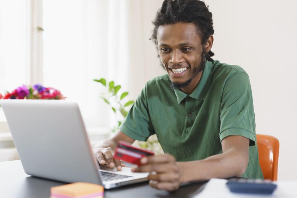 Happy man shopping online through laptop at home