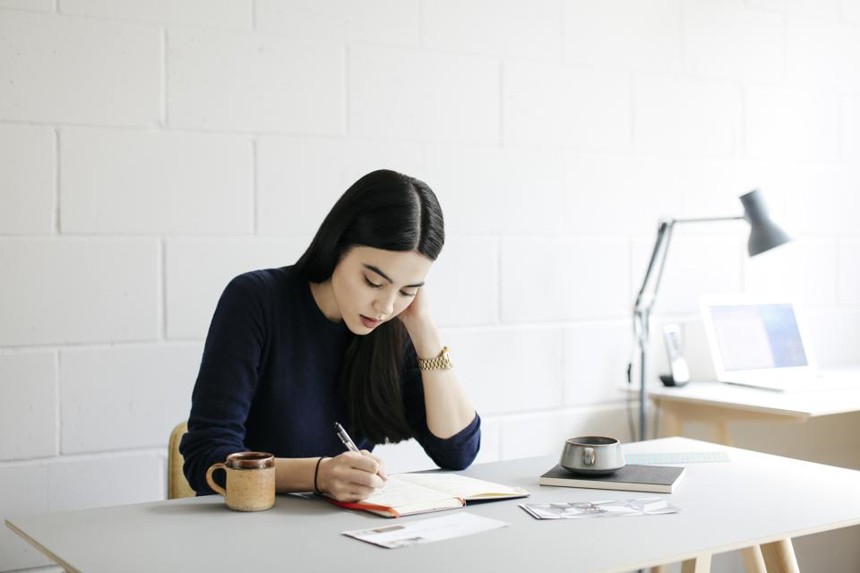 young woman taking notes in creative studio space