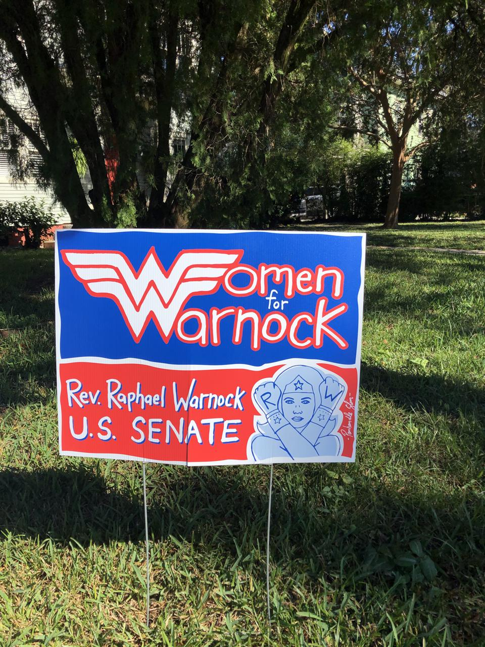 A Women for Warnock sign by Panhandle Slim.
