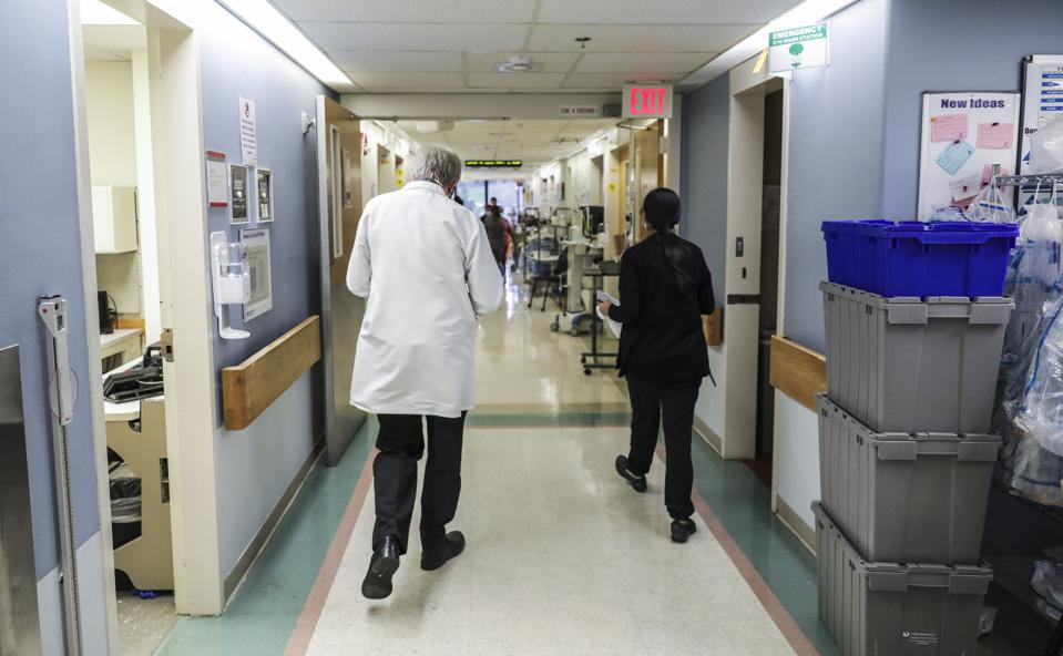 A doctor is seen walking down the hall of an ICU floor at UMass Memorial Hospital