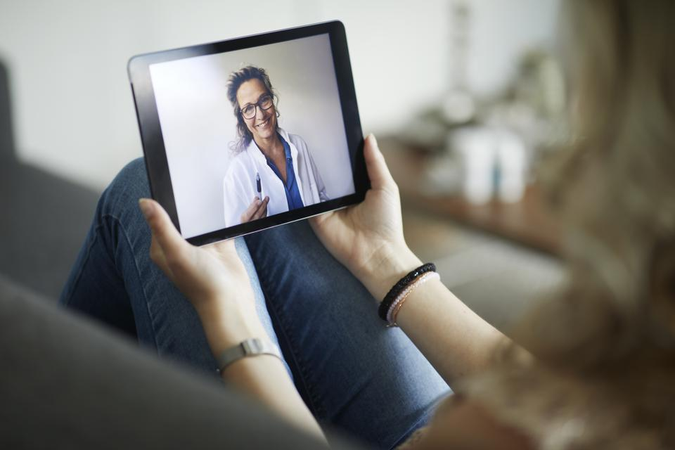 Young woman having online meeting with female healthcare person