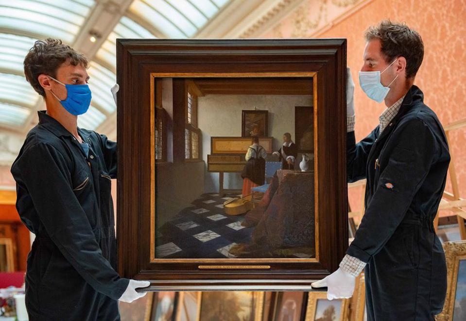 Two men in masks with a Vermeer painting