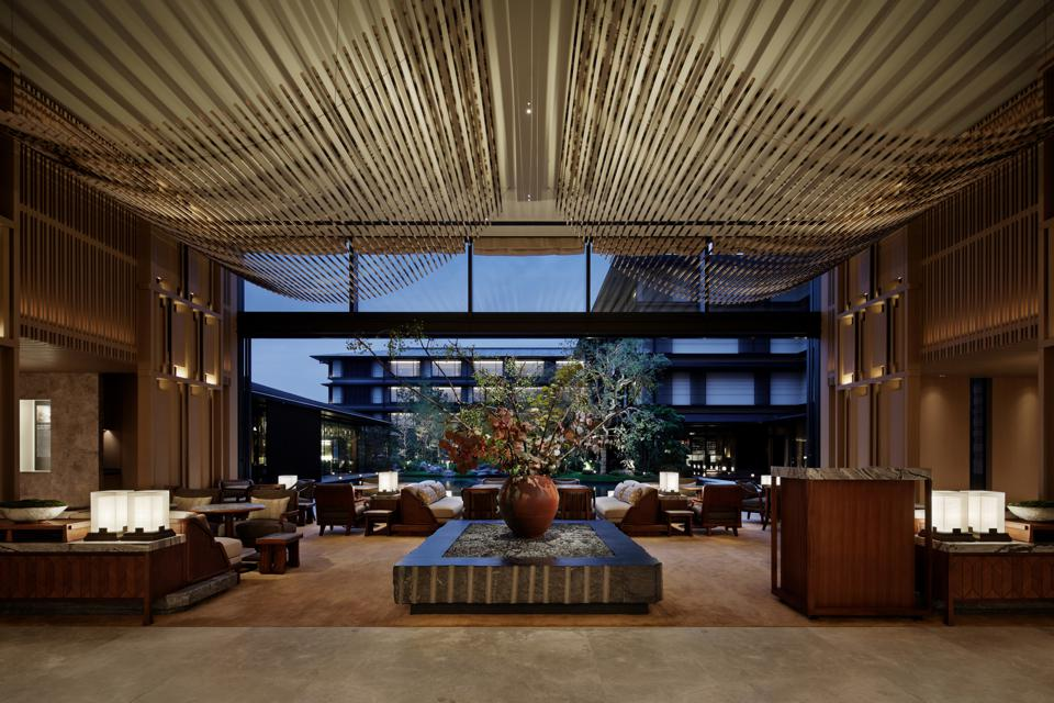 An expansive room with a golden sweep of rods draped from the ceiling overlooking the outdoors