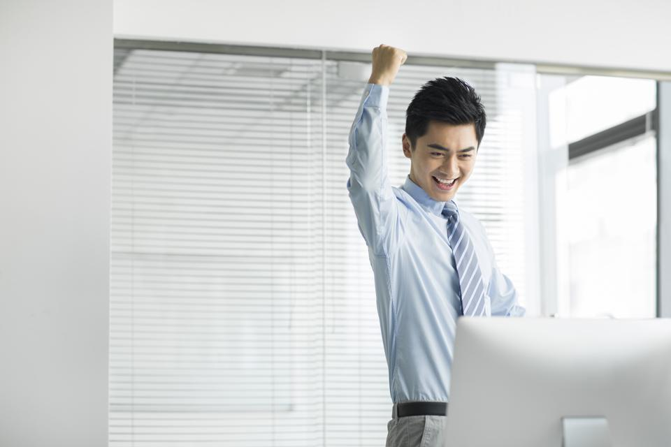 Cheerful young businessman using computer in office